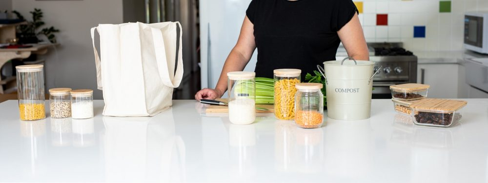 looking at a white kitchen bench with a canvas shopping bag, glass pantry containers, a kitchen compost bin and a chopping board and celery on it