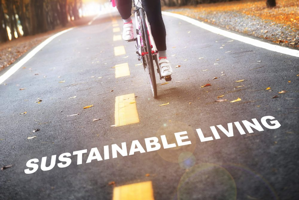 bottom half of bike riding towards camera in the middle of the road with the caption 'sustainable living' underneath