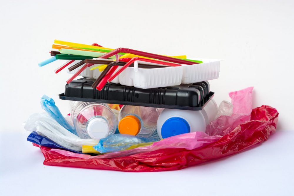 A pile of single use plastic garbage including water bottles, drinking straws, food packages and carrier bags on white background with copy space. Pollution concept