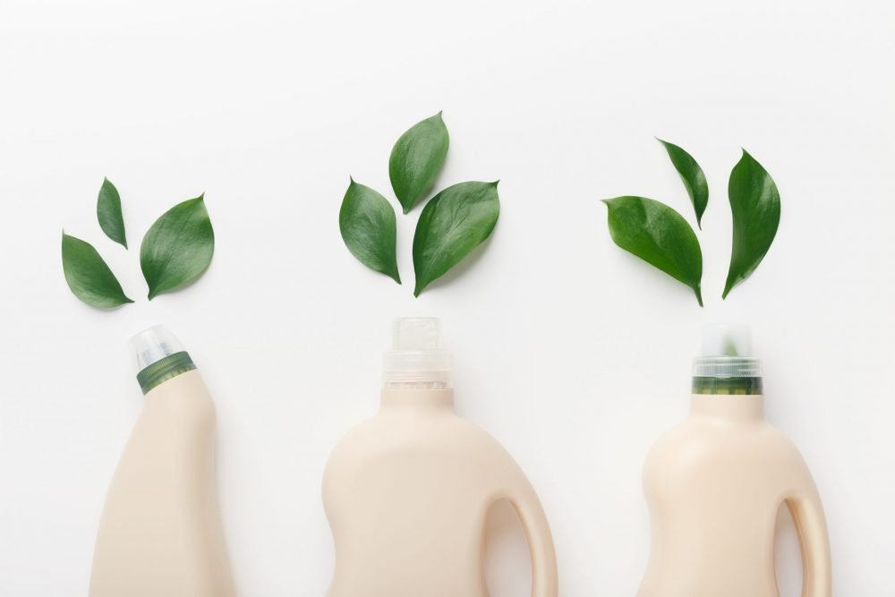 white background with three natural coloured detergent bottles with green leaves looking as though they are coming out of the bottles