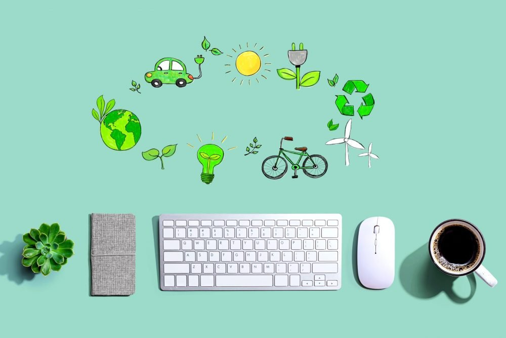 aerial view of light green desk with a keyboard, mouse and black coffee and above a circle of sketched green images - car, world globe, leaf, lightbulb, bicycle, recycling symbol, sun