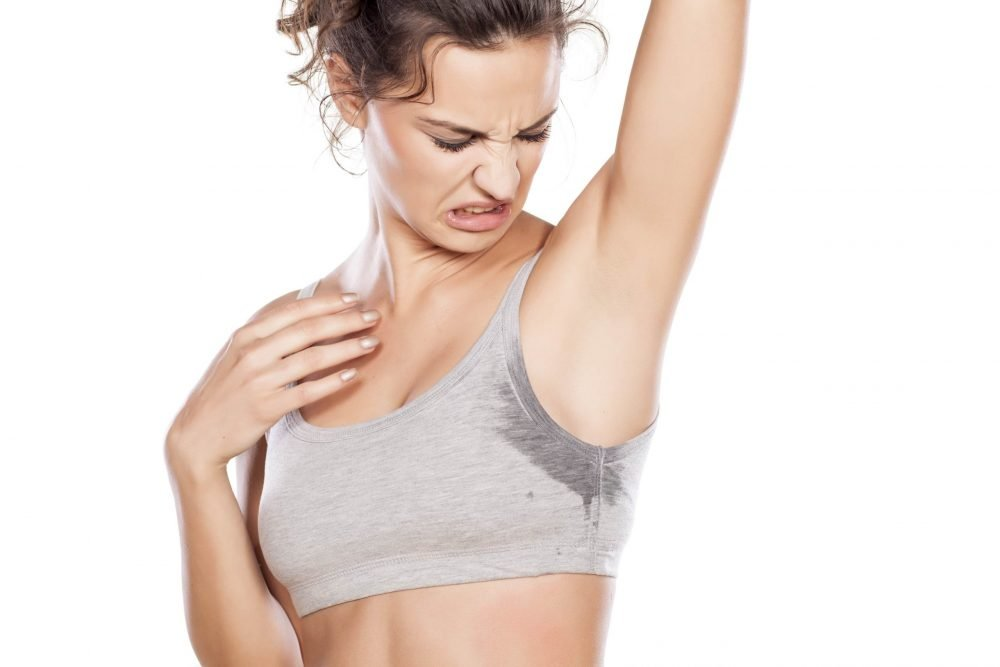 Woman in active wear looking at her sweaty armpit in disgust